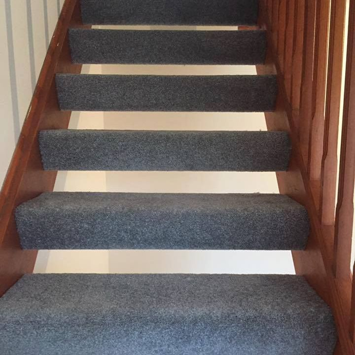 Wrap around blue stairs carpet on an open stair case