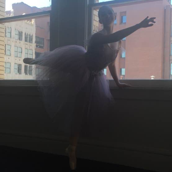 Ready to perform, this level 6 ballet dancer balances on pointe before she takes the stage.