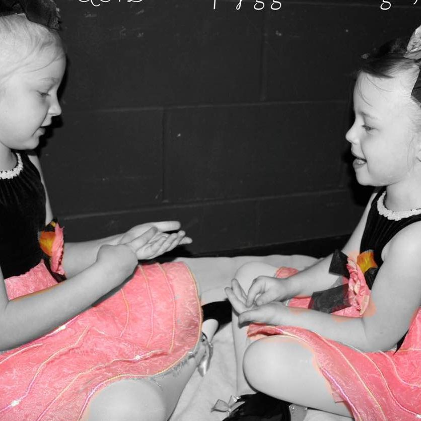 4 year olds play games together while they wait their turn to dance onstage.
