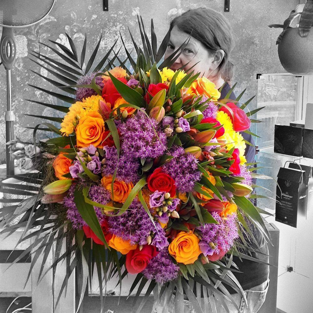 Nicole Tiwisina mit einem großen bunten Blumenstrauß im Blumenladen Tiwis Blütenzauber in Düsseldorf.