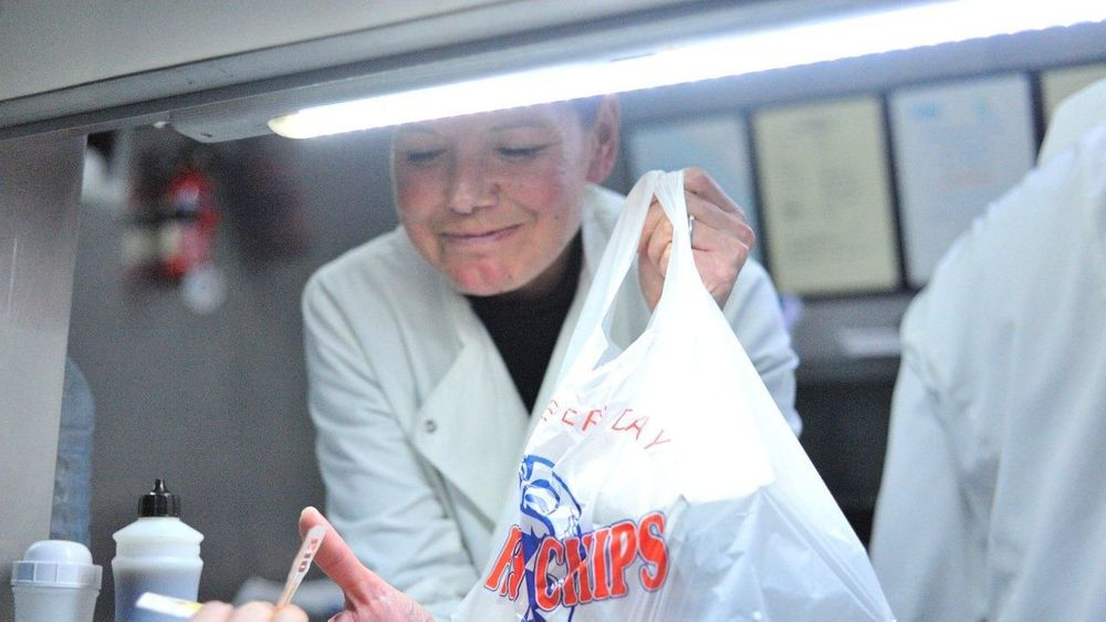 Owner Amanda in her chefs whites giving a carrier bag full of tasty fish and chips to a customer from the fish and chip van serving hatch in Methley.