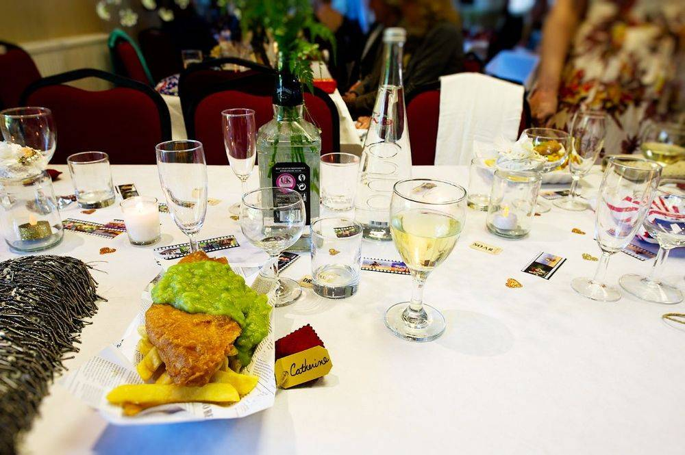 A portion of wedding fish and chips with mushy peas, on the bride and grooms banquet table strewn with celebratory empty drinks glasses.