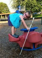 Little blind girl with purple glasses standing on a playground toy stooped over holding a round handle and her long, white cane. She is wearing a light blue top with dark blue shorts. She is smiling and has short, blond hair.
