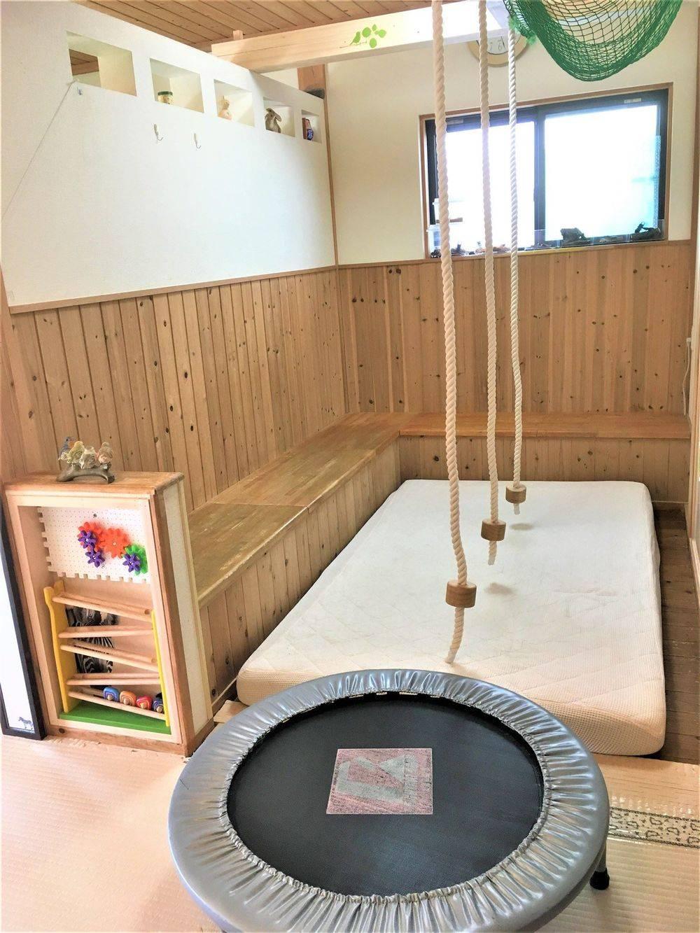保育室内アスレチックエリア 雨の日でも室内で発散できるように アスレチックエリアをオープン!  段差のある床、3人分のぶら下がりロープ、 マットにジャンプしたり、ボールプールにしたり、 トランポリンや滑り台を出すスペースとして 活用しています。 年齢・月例に応じた室内遊びが出来るよう 工夫を重ねています。