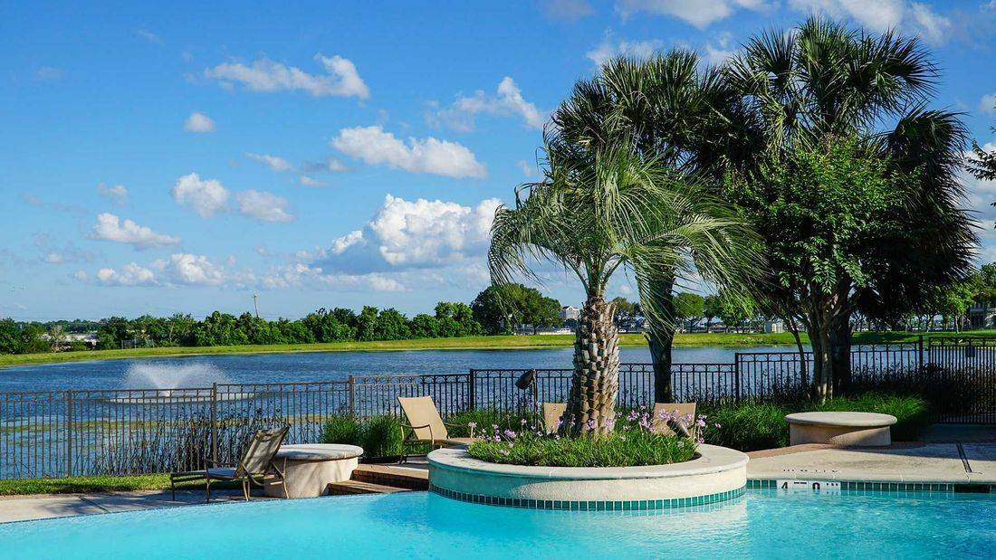 Clear Lake luxury apartments, pool overlooking the lake, golf course, garages, on site lake,  lush landscaping, palm trees