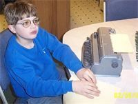 Young blind boy wearing glasses and a blue sweatshirt reading braille at a table with a loaded braille writer next to him.