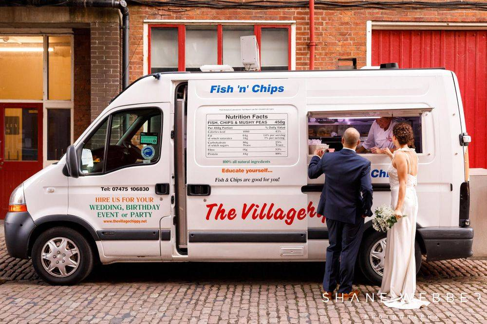 Newly married bride in her beautiful long pencil wedding dress and groom, having their wedding breakfast from the hired fish and chip van serving hatch.