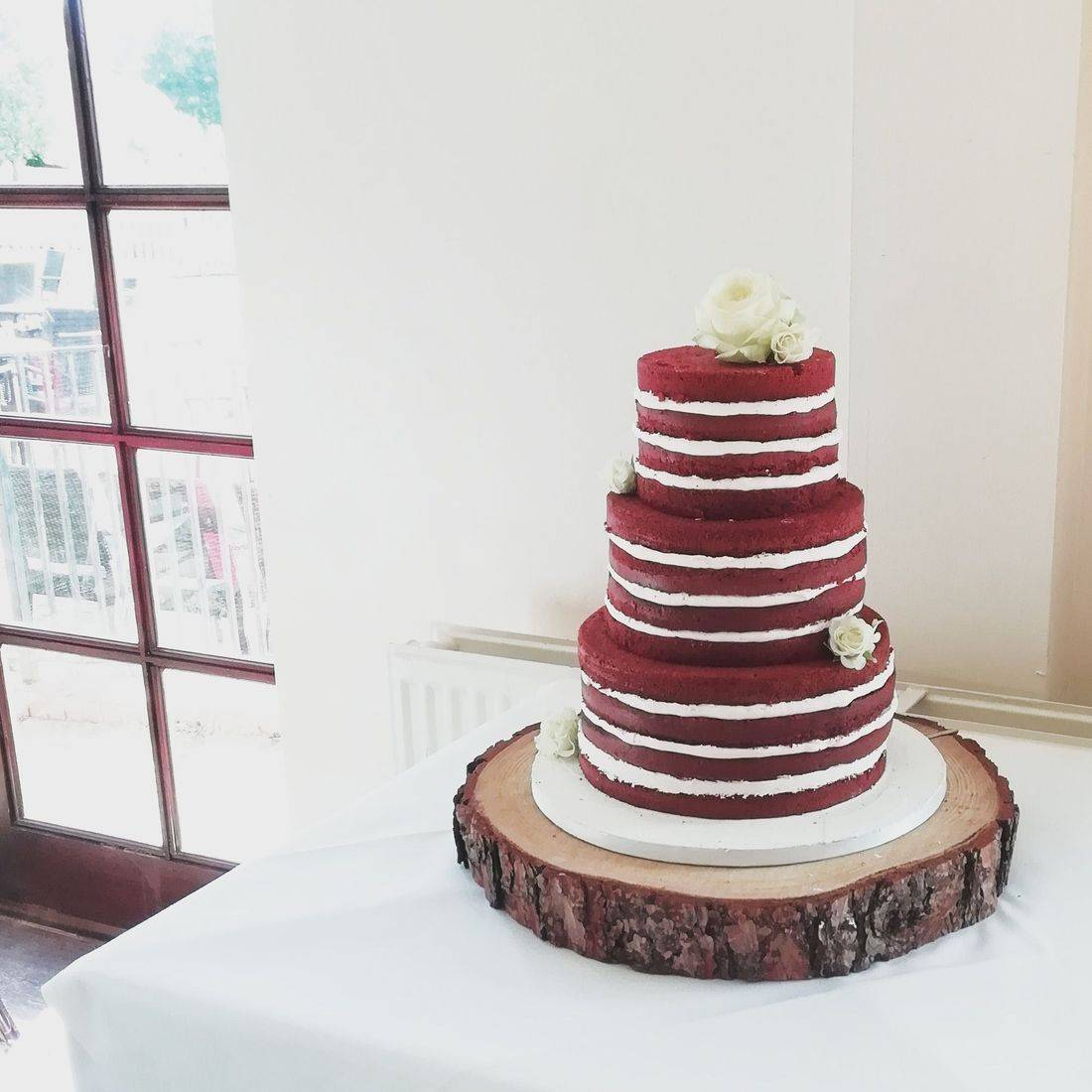 3 tier red velvet naked cake with fresh flowers and buttercream on a log stand