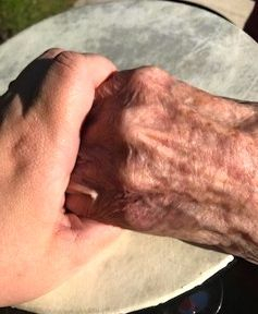 Older adult holding hands playing drum music therapy