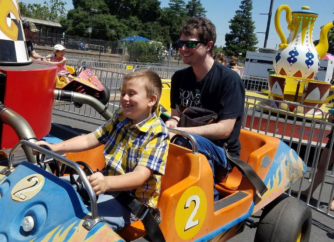 Blind child, blind young man, carnival, ride, big smiles