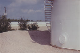 Clay dike liner for Storage tank dike; Storage tank containment dike reline with clay and dressed up with washed gravel.