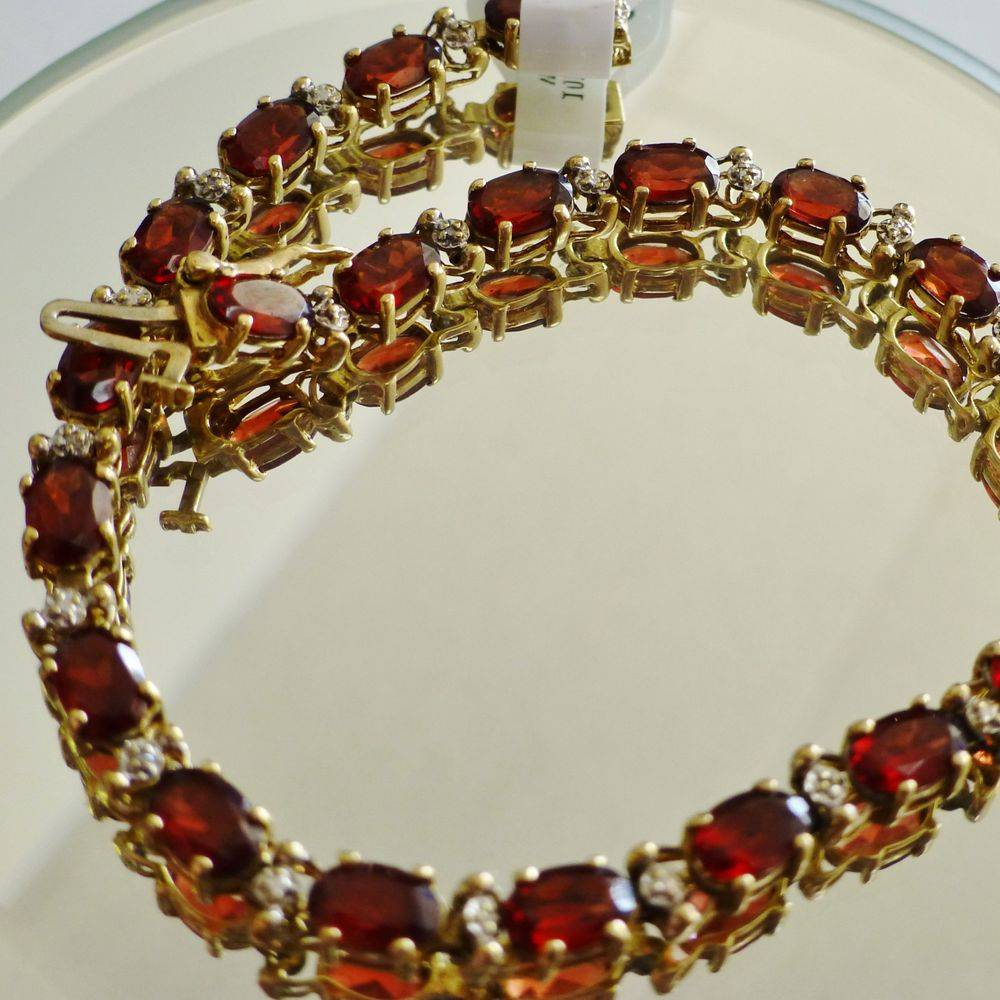 closeup picture of a yellow gold oval cut garnet diamond accent tennis bracelet