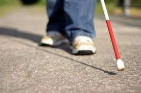 Person walking with cane on pavement