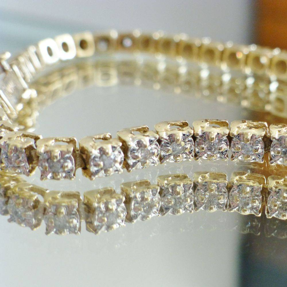 Closeup picture of a diamond tennis bracelet in yellow and white gold