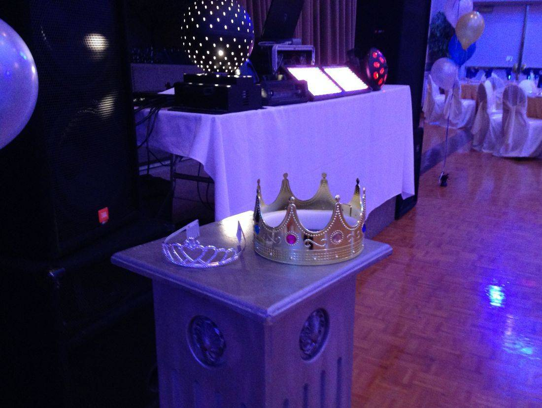 prom king and queen crowns with dj setup behind
