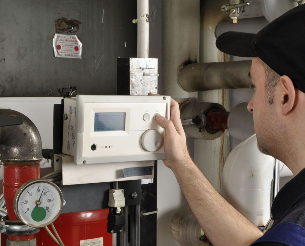 Service technician adjusting the temperature on a boiler system