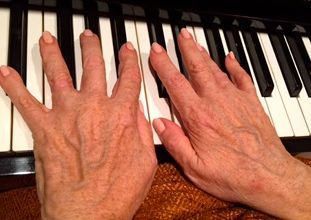 hands of older adult playing piano music therapy