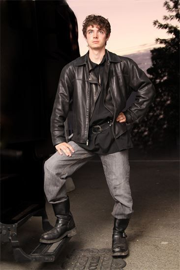 Brandon Keith Biggs, LCA-CRB1, in The Godesses of Etros as a Space Pirate.Young blind man posing with a leather jacket, grey pants, and tall black boots, with one foot up on a ledge