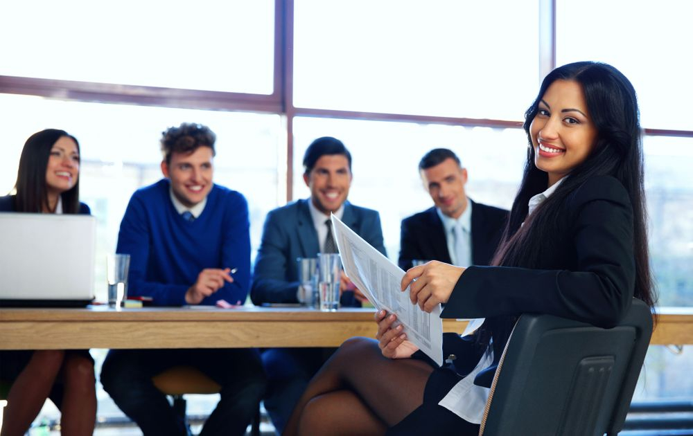 Pictured here is a woman with long hair in business clothing turned towards the camera smiling. She is holding documents in her hand and her legs are crossed. She is sitting at a table, populated by four other people on the other side smiling at her. On the left is a woman on a laptop, next to her on her right is a man in a blue sweater. On his right is another man in a light blue business suit. Next to him is a man with a black business suit. They are in a business meeting in an office setting with large windows behind them.