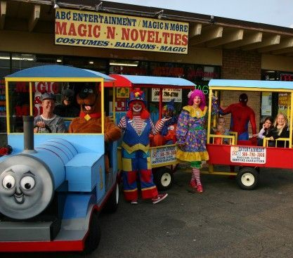 Thomas the trackless train with 2 passenger cars and clowns standing in front