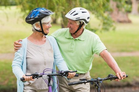 Senior couple riding bikes outside during the summer