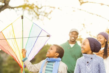 Young family flying kite in fall