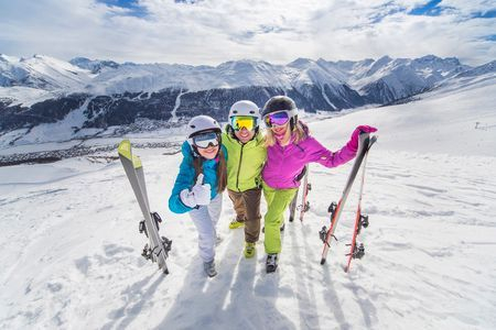 Young people skiing and snowboarding on the mountain
