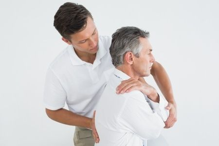 Male chiropractor adjusting male patient