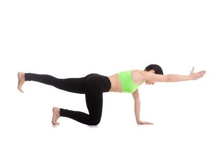 Woman performing bird-dog back exercise