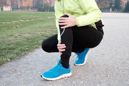 Runner kneeling down holding leg pain in winter