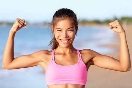Happy woman flexing arms on the beach