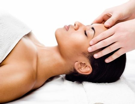 Woman receiving head massage from therapist