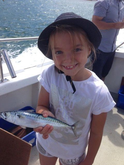 Young girl holding a mackerel