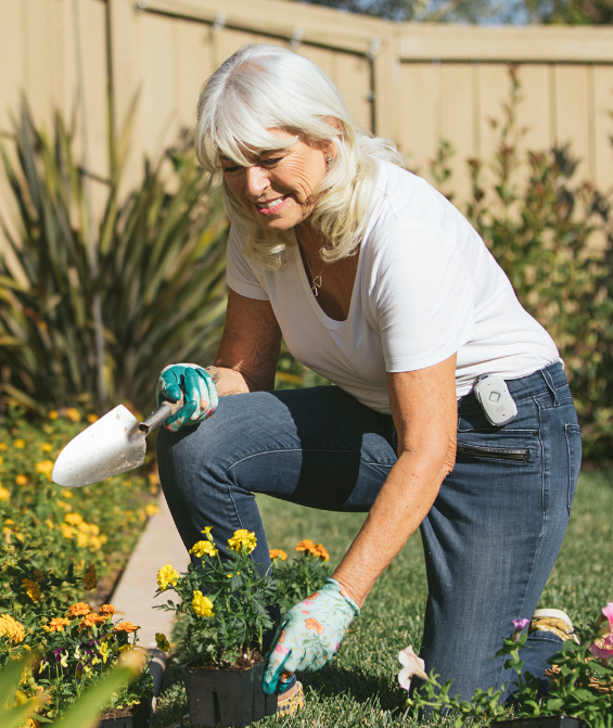 AGING IN PLACE - Women Gardening and wearing her GPS Safe on the go device.
