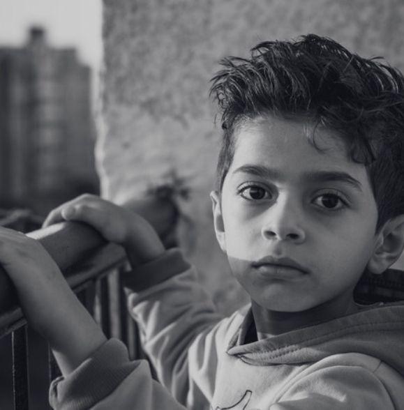 image of child facing camera hands on railing