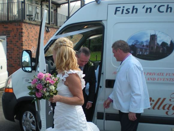 Bride in her wedding dress with the groom exiting the wedding fish and chip van after being driven from the church to the reception.