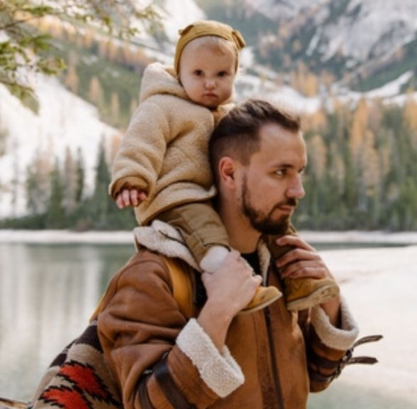 image of man carrying toddler on shoulders