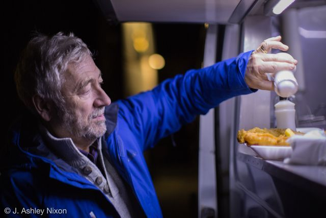 Thorner customer at night at the brightly led lit fish and chip van serving hatch, putting plenty of salt and vinegar on his delicious freshly cooked fish and chips.