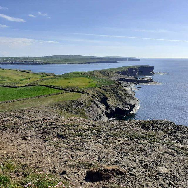 view from clifftop along coastline with blue sea