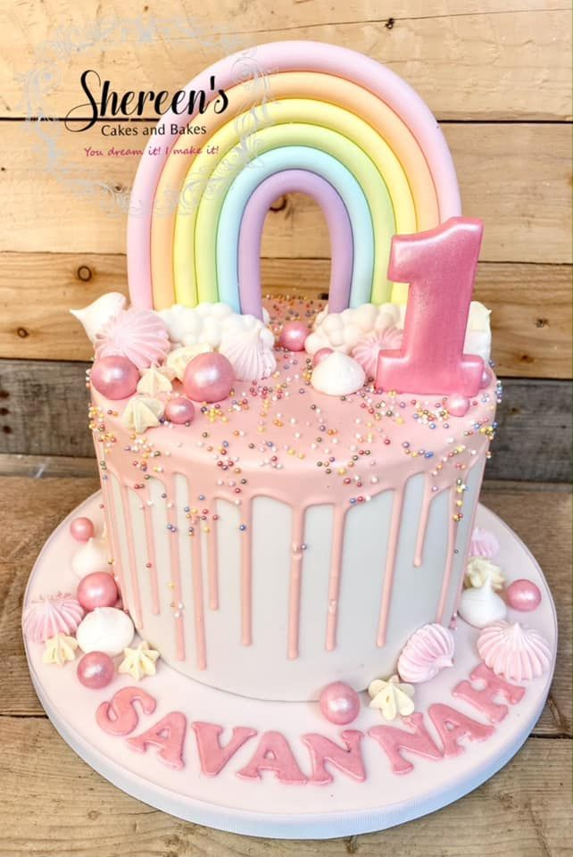 Pink drip cake with pastel rainbow and meringues