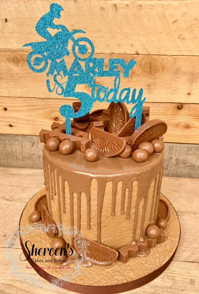 Drip cake topped with a personalised topper and loads of chocolate