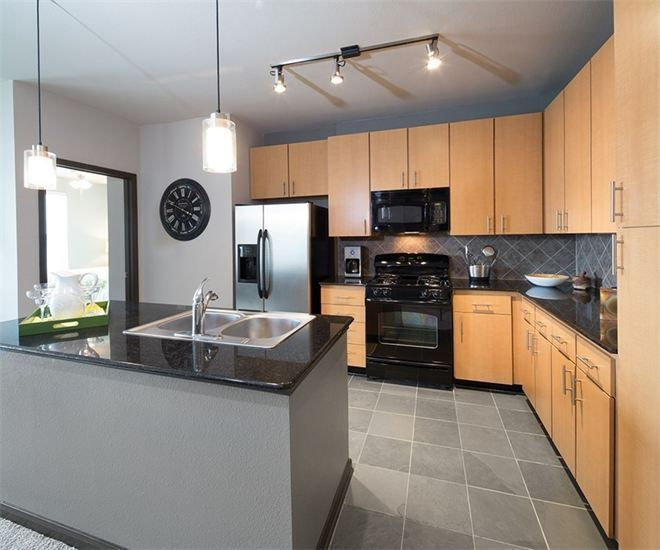 Apartment kitchen, custom cabinetry, island, floor to ceiling windows, pendant lighting, stainless and black appliances,