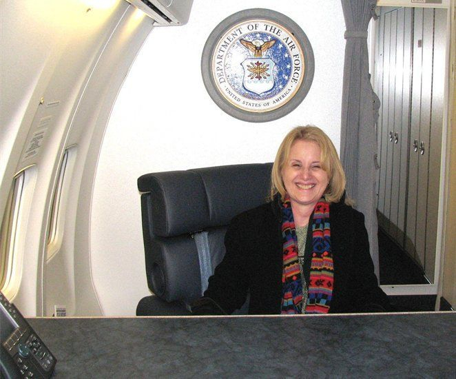 Rhoda aboard Air Force 2 sitting below the seal of the Department of the Air Force