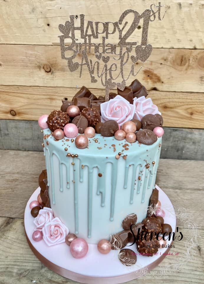 Topped with chocolates, roses and pretty gold elements and personalised cake topper