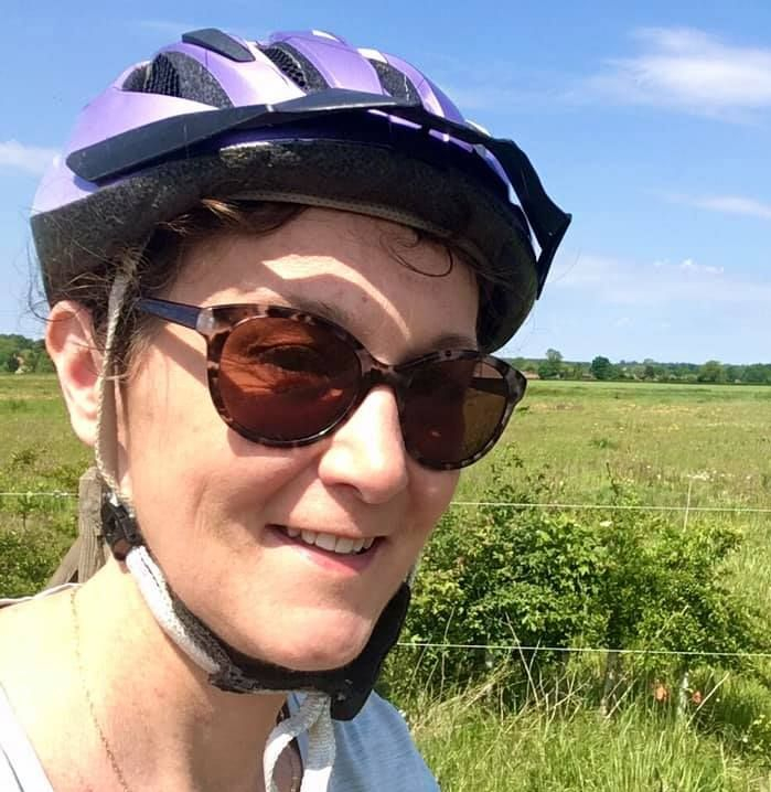 Angie Giles wearing bicycle helmet near a field