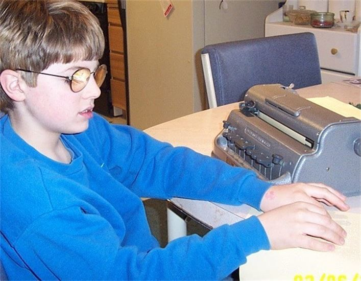 Young boy wearing glasses, reading braille, with braillewriter beside him.