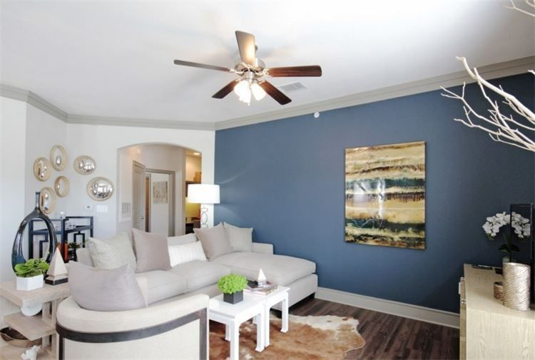 apartment living room blue wall ceiling fan and archway