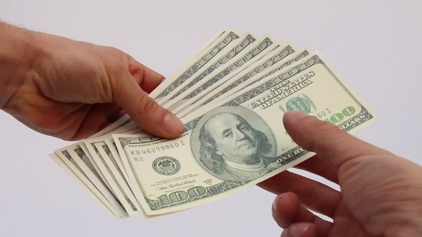 Hands Exchanging Money For A Pawn Loan
