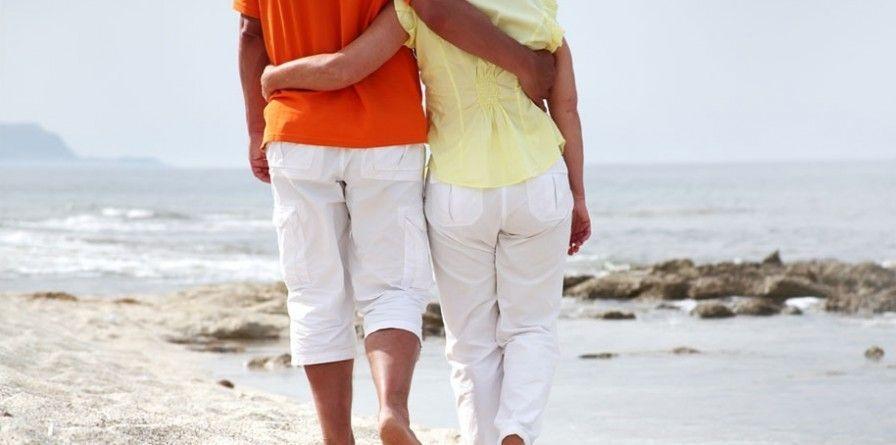 Couple walking on the beach barefeet