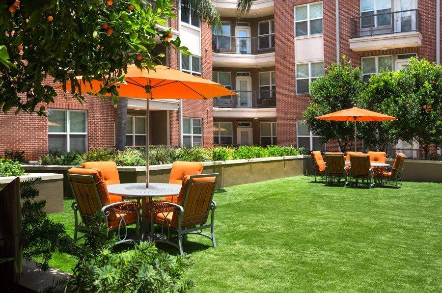Greenway Plaza apartments courtyard with tables, chairs,  grassy area